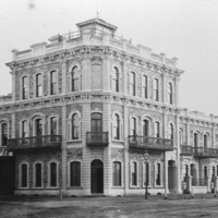 Image: a large, stone, three storey corner hotel with adjoining two storey terrace houses. The windows on both the hotel and houses are arched and the roofs flat. The houses have bay windows on the first floor and balconies on the second.