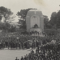 Image: A large crowd of people in 1930s dress or military uniforms gather around a huge stone monument featuring three bronze statues of a girl, a student and a farmer in front of a large marble angel.