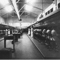 Image: A telephone exchange. There are two rows of switchboard operators on either side of the image, separated by a floor and desks.