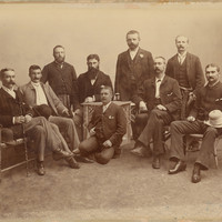Image: nine men posing for a portrait, six are seated, four are standing