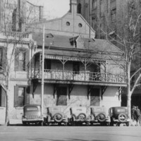 Image: 1930s era cars are parked on the street outside a two-storey stone building with shuttered windows and a balcony running halfway along the front of the building.