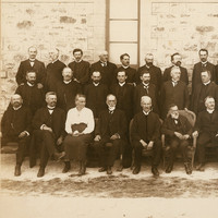 Image: Black and white group portrait. Three rows of men in suits pose against a stone building. There is one woman in the photograph. She is seated in the front row, third from left.