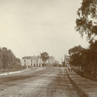 Image: a wide, muddy road stretches through parklands. In the distance the road continues through a more built-up area with numerous buildings including a corner hotel.