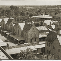 Image: an aerial view of a complex of one and two storey stone buildings with slate and tin roofs including one with verandahs under which 1930s cars are parked.