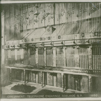 Image: Black and white photograph of a telephone exchange. There are no people present