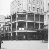 Image: A five storey corner building with balconies on the second and third floors.