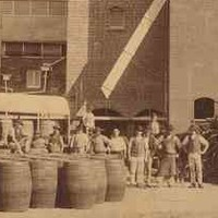 Image: a group of men in late 19th century worker's clothes stand with a collection of large barrels outside of a tall red brick brewery building.