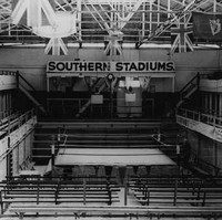 Image: A large, empty swimming pool in a vast open building with a roof. A wrestling ring is positioned within the empty pool