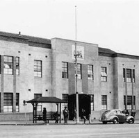 Image: A two-storey building with plain façade at the intersection of two streets. 1940s-era auto-mobiles and pedestrians are on the street in front of the building