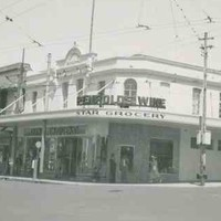 Image: a two storey corner grocery store with a self supporting verandah. The building is painted white. There are a number of pedestrians and 1950s era cars on the street outside.