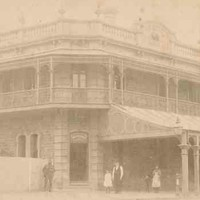 Image: a two storey corner hotel with a narrow wrap around balcony and balustraded parapet with urn decorations. On one side of the ground floor a wide verandah protrudes beyond the balcony above.  The other side is fenced off.