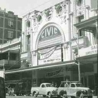 Image: 1950s era cars are parked outside a large theatre building which features a huge decorative arch inside which is a sign with the theatre's name and information about the current show. The building also features decorative plasterwork.
