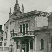 """Image: a girl stands outside a simple two storey stone building with protruding wooden balcony and a sign reading """"Queen's Chambers"""". Behind the building the spires of a small church can be seen."""