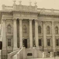 Image: A large three storey stone building with a columned portico entrance on the second floor. Two stone staircases curve up to the grand entrance which is flanked by four stone columns. The building has a flat roof with a balustraded parapet.