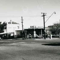 Image: A 1960s era shell service station, with a car with its bonnet up parked under the overhanging roof, sits on the corner of two city streers