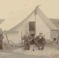 Image: Four men sit on chairs in front of a tent. One man holds a bicycle while two others brandish rifles