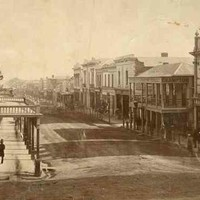Image: a view of a city street which is lined with two and three storey commercial buildings. A large number of male and female pedestrians in 1860s attire can be seen walking down the sidewalks or crossing the road.