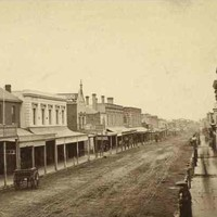 Image: a view of a city street lined with two storey commercial buildings, many of which on one side of the street have verandahs or balconies while most on the other side have flat facades. On the left, a large model of an emu stands above a verandah.