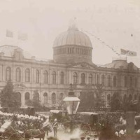 Image: a large crowd of people in 1880s clothing gather in front of a large building with a domed roof watching as horse drawn carriages pass by.