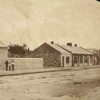 Image: men and boys in 1860s attire stand on a paved sidewalk outside their cottages.