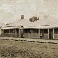 Image: a row of three identical brick, iron-roofed cottages with fenced in verandahs. A group of four children stand with their mother outside the rightmost cottage. On the far left is a fourth building which is being used as a general store.