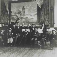 Image: members of a small band, both male and female, pose with their instruments in front of a small stage dressed with a backdrop featuring a castle.
