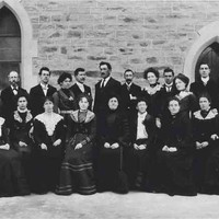 Image: men and women in dark coloured clothing pose in two rows for a formal photograph.