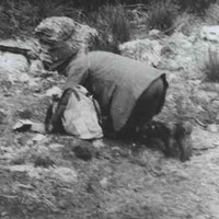 Image: A man in a hat and outdoor clothing is poised on all-fours and looking intently at the ground. A light-coloured bag is on the ground next to him