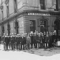 """Image: A group of men wearing 1920s era suits and holding their hats pose for a photograph on a street corner outside a building with a sign reading: """"S.A. Soldiers' Fund"""". To one side are two more men who only have one leg."""