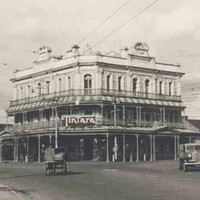 Image: a large, three storey, corner hotel with wrap around balconies on the two upper floors and an ornate parapet