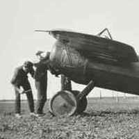 Image: Three men stand next to a First World War-era monoplane parked on a large, flat expanse of ground