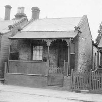 Image: a row of tiny stone workers cottages with brick quoins, a single door and window beneath a verandah on the front elevation, pitched tin roofs and small lean-tos on the rear.