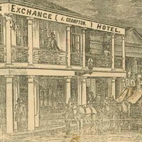 Image: A coach and four stands outside the Exchange Hotel, a two storey building with large windows on the ground floor. A lady and gentleman look on from the balcony.