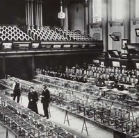 Image: Two men and a woman stand in a large open room with four large tables arrayed in rows. On each table are several cages, each of which contains one live bird