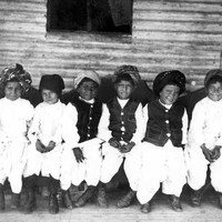 Image: A group of children in traditional Afghan clothing sit on the verandah of a rural home
