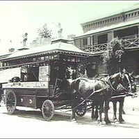 Image: a man in early 20th century clothing stands by a horse drawn tram which is parked in front of a two storey house.