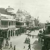 Image: A view of a city street with many people in 1920s attire walking, riding horses or driving motor vehicles. The street is lined with 2 and 3 storey commercial buildings, most with verandahs and/or balconies and a number featuring towers with domes.