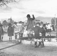 Image: A group of children stand near the edge of a pond in a playground. One child balances on the edge of the pond. A flagpole and playground equipment are visible in the background