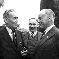 Image: Three men in suits and ties speak with one another on a property's well-manicured grounds. Each man is smiling, suggested he is amused by the conversation