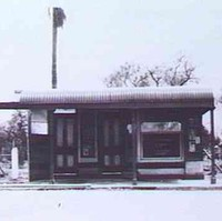 Image: A single-storey shop with two front doors, a front window, and corrugated metal awning