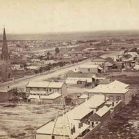 Image: Several houses, buildings and a church border a long, dirt street