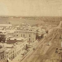 Image: Several buildings border a large dirt road. Horse-drawn carriages and people are visible in the road