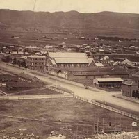 Image: A large open fenced paddock is surrounded by two dirt streets, buildings and houses. Large hills are visible in the background