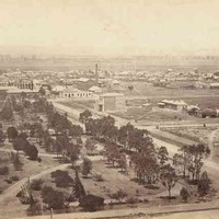 Image: A large park bordered on one side by a dirt street. Several buildings and houses are visible in the middle distance