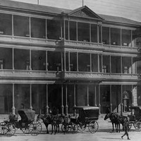 Image: A line of horse drawn vehicles waits outside a huge three storey hotel with balconies on the second and third floors and a verandah on the ground floor.