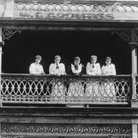 Image: a group of five women in white dresses in an early 20th century style stand on a balcony of a two storey building which has signs declaring it the Globe Dining Rooms