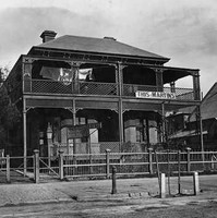 Image: a two storey building with a combination verandah and balcony, decorated with lattice work, sits behind a wooden fence. Washing dries on a line on the balcony.