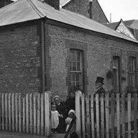 Image: A family in Victorian attire stand in front of a rectangular, single-storey stone and brick building. A white picket fence surrounds the building, and a few multi-storey stone and brick structures are visible behind it
