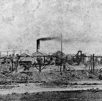Image: Smoke billows from the chimney of a low building surrounded by mining equipment