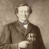 Image: An old photograph of a man wearing a dark coat, bow-tie and medals posing with one hand holding a book upright on a table by his side, the other, his right, tucked in between the buttons of his coat